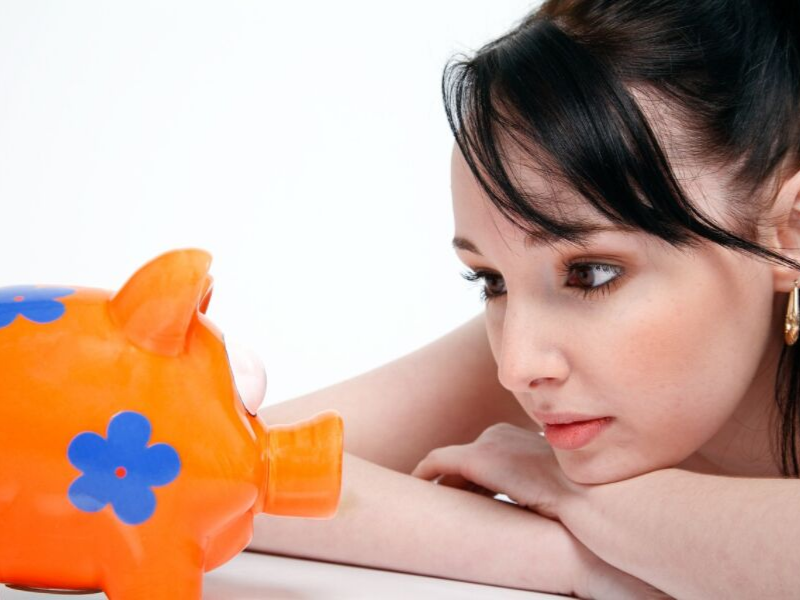 woman staring at a piggy bank
