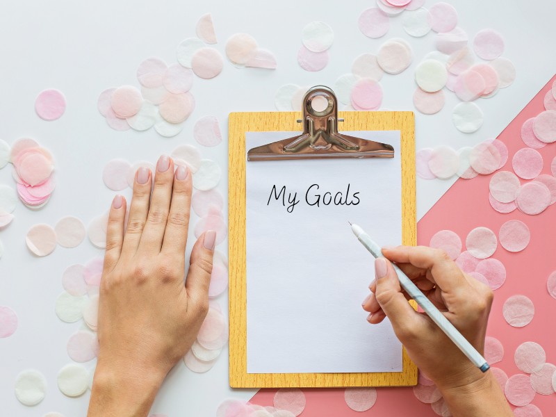 woman writing goals on clipboard
