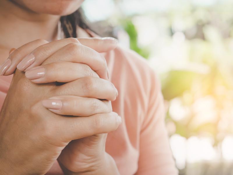 woman folding hands in prayer