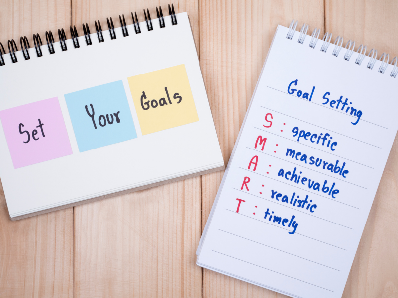 2 noteboks, one with post its set your goals other with Smart goals defined