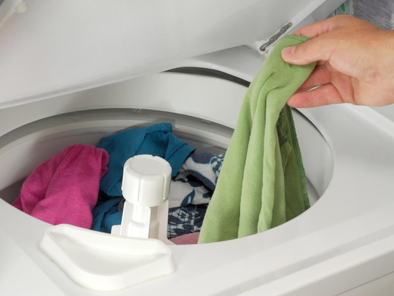 putting clothes in a washer