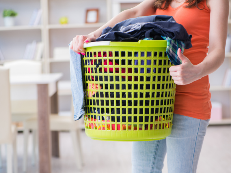 woman carrying filled green laundry basket